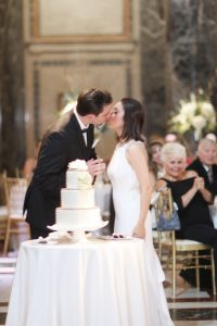 kissing behind wedding cake