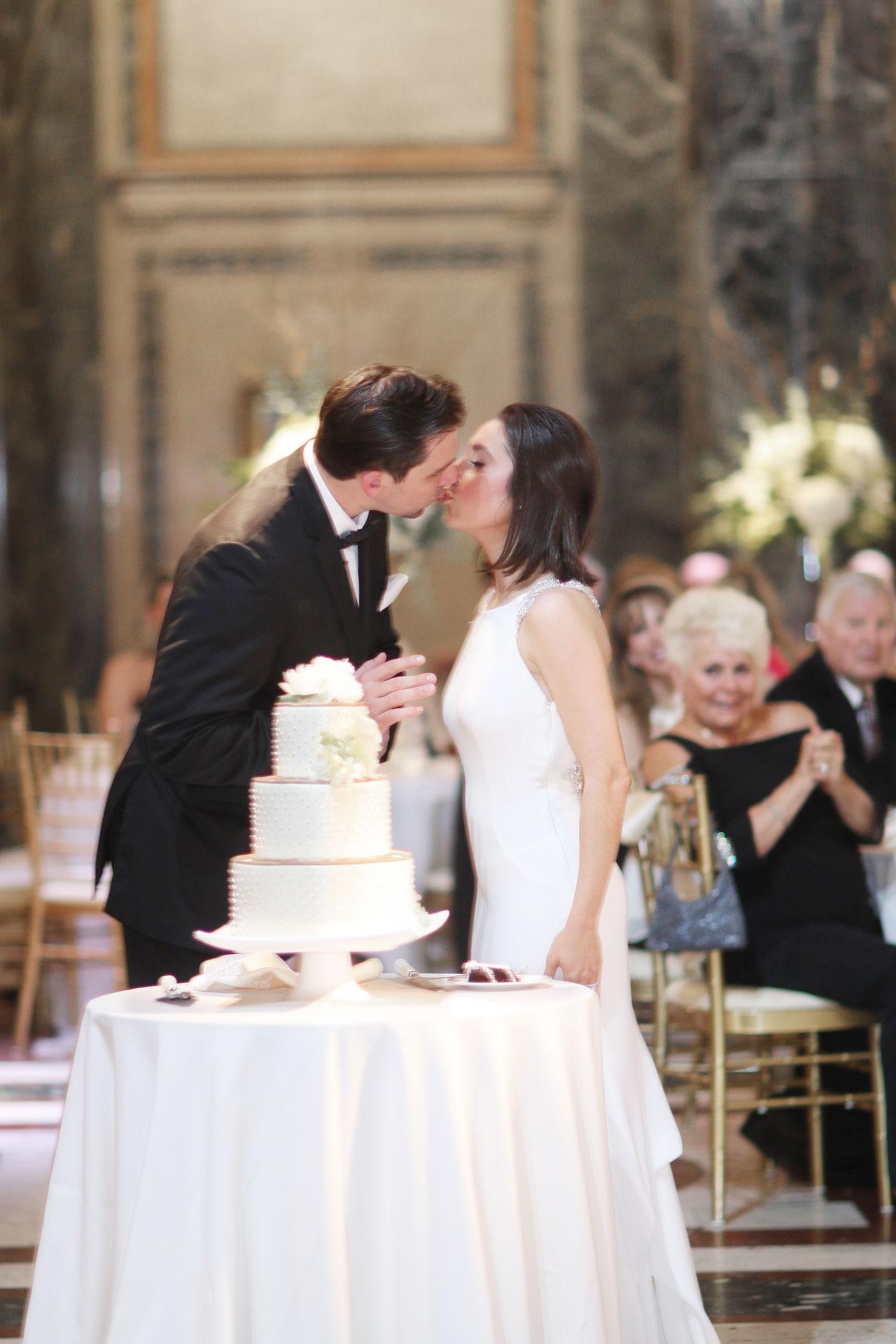 kissing behind wedding cake