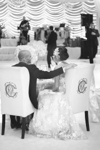 bride and groom sitting in monogrammed bridal chairs