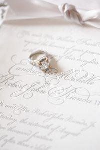 diamond wedding ring sitting on invitation