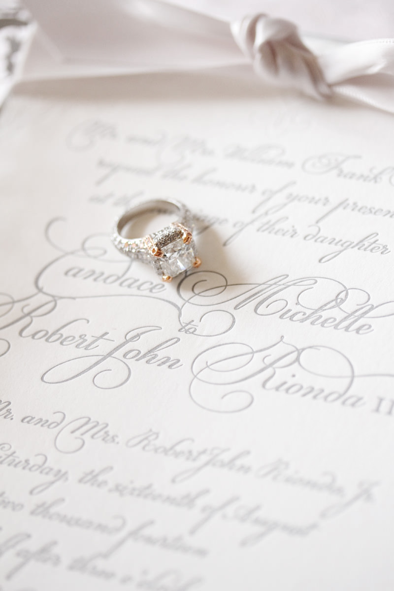 diamond wedding ring sitting on invitation