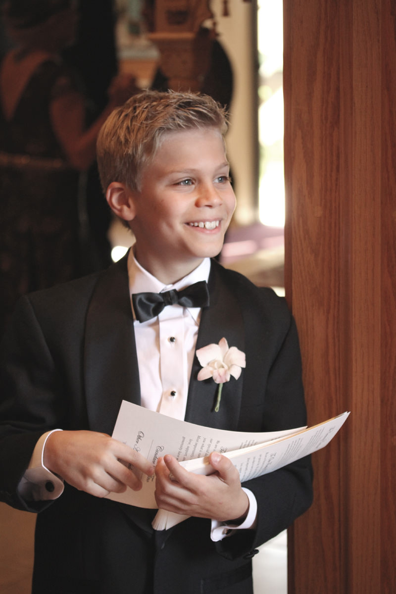 young boy handing out wedding programs