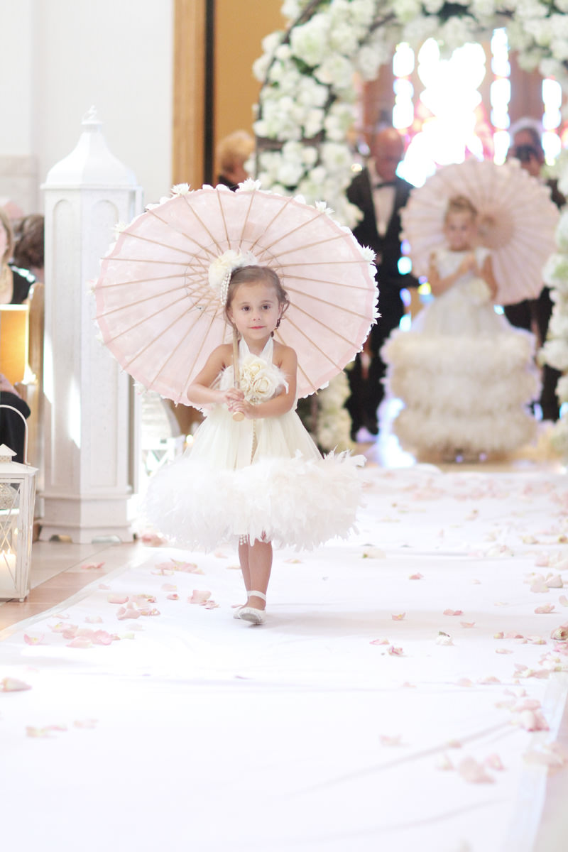 young girl walking down aisle at wedding carrying parasol