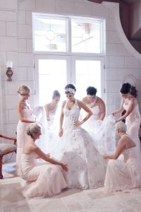 bridesmaids tending to brides dress