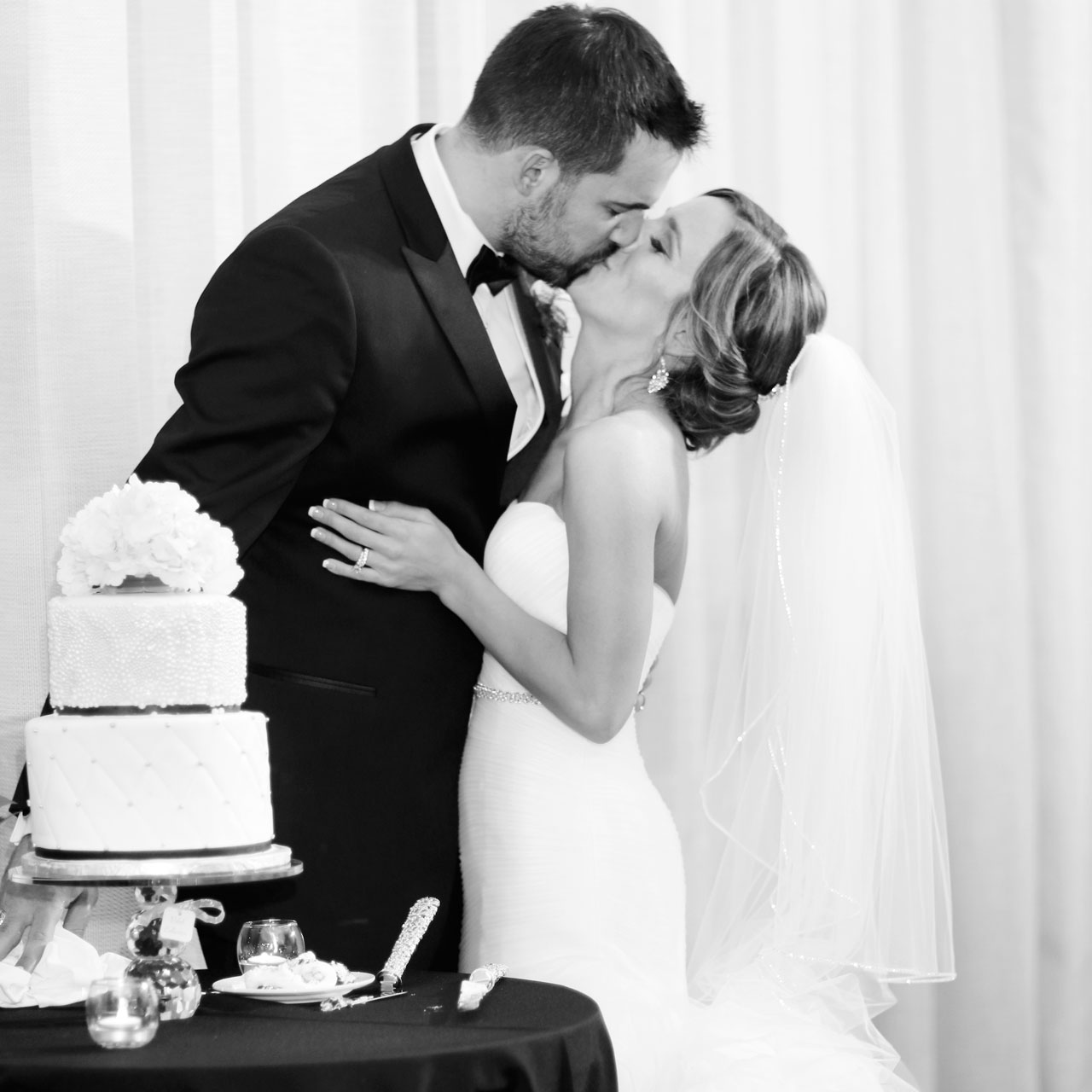 bride groom kiss by cake