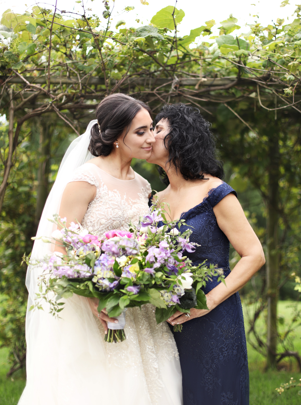 mom kissing bride daughter
