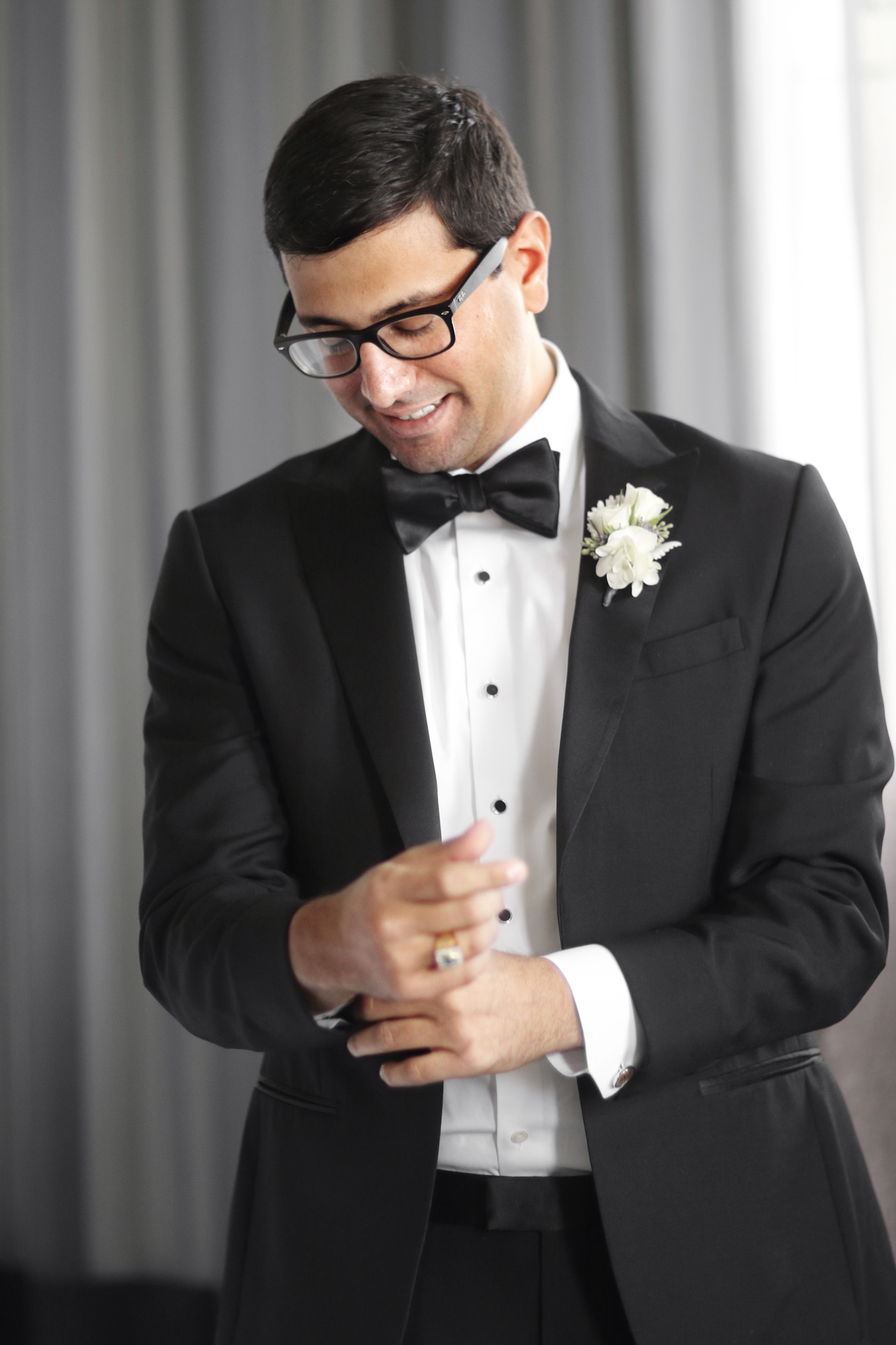 A groom adjusting his cuff links