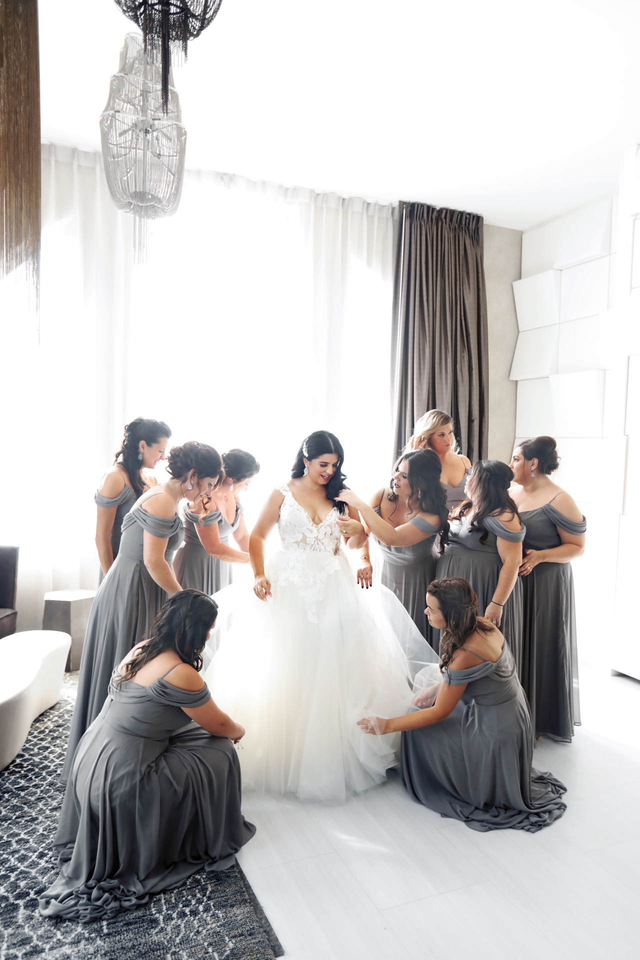 bridesmaids assist the bride before the wedding ceremony