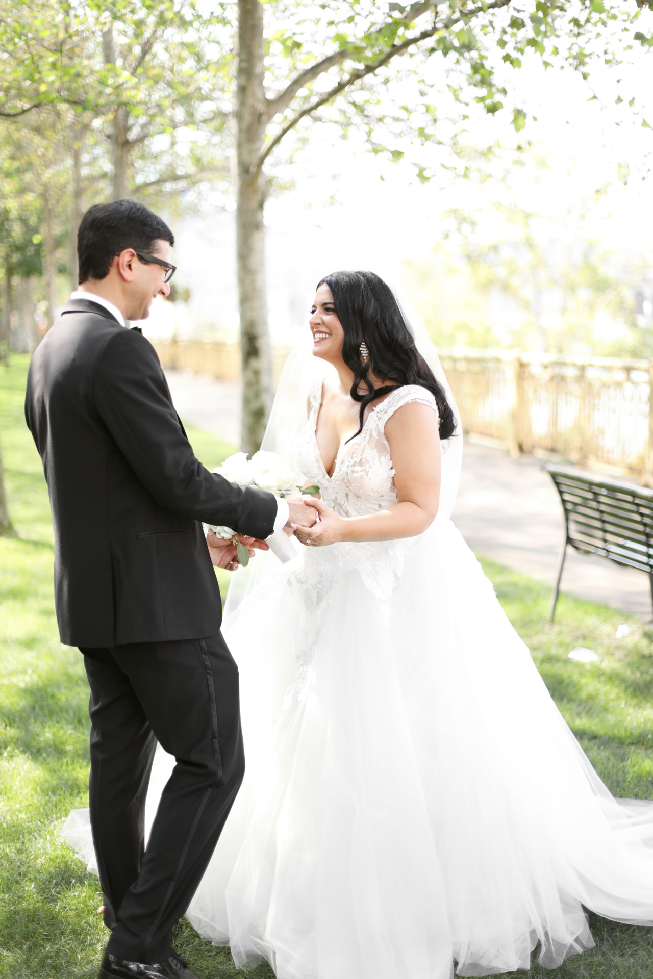 A bride and groom share a happy moment in the park