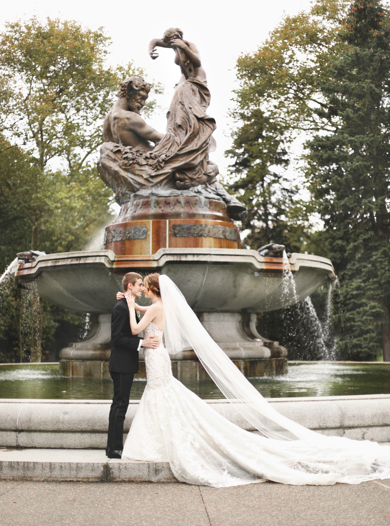bride and groom standing by fountain in pittsburgh, pa