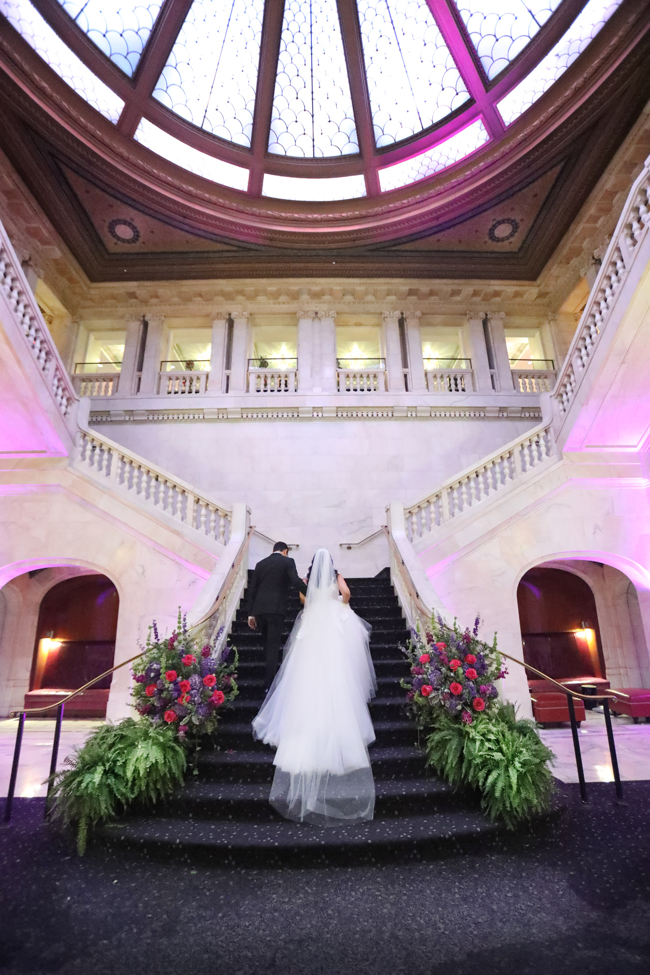 bride and groom walking up the grand staircase at the Renaissance Hotel