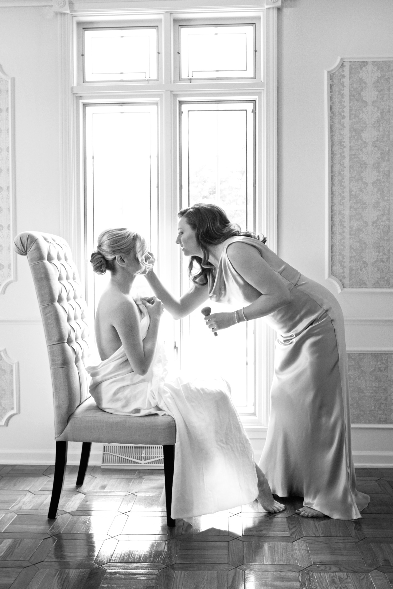 a bride getting her makeup applied by a bridesmaid